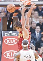 Cleveland Cavaliers' Anderson Varejao dunks in front of Miami Heat's LeBron James (6) during the first half of a game Tuesday in Miami.