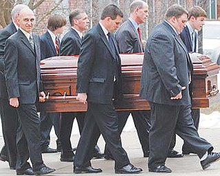 Pallbearers including sons Jay Paterno, foreground right, and Scott Paterno, foreground center, carry the coffin of former Penn State coach Joe Paterno after funeral services at the Pasquerilla Spiritual Center on the Penn State campus Wednesday in State College, Pa. Paterno, 85, died of lung cancer Sunday morning.