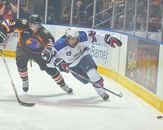Youngstown Phantoms defenseman Chris Bradley (3) closes in on Team USA's Tyler Motte during a recent game at the Covelli Centre. Bradley was selected last week's USHL Defenseman of the Week.