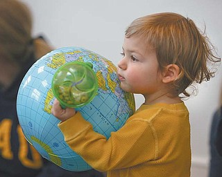 William Garrett, 21 months, of Canfield, carries the world in his hands at a Baby Brilliant early-literacy session at the Poland Branch of the Public Library of Youngstown and Mahoning County.