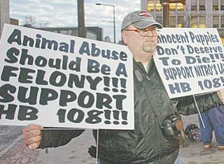 Mike Smeck, of Amherst, Ohio, was one of a small group who gathered Tuesday in downtown Youngstown to rally against the abuse of animals. Smeck and others held signs supporting House Bill 108, or Nitro's Law, which would make animal abuse inside a kennel a felony offense.