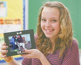 Maddi Graham, a seventh-grader at Akiva Academy in Youngstown, holds a picture of Dahlia the Dalmatian, who
