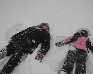 Mia Lazazzera, 5, of Canfield, makes snow angels with her grandma, Theresa Panezich, while visiting in Edinburg, Pa. Photo taken by Mia's mom, Mindy Lazazzera.