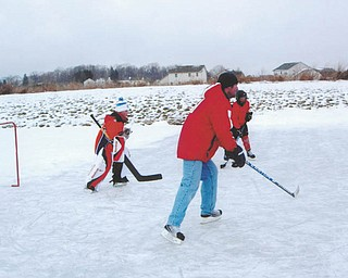 Goalie Trey Imhoff, and his dad, Bernie Imhoff, both of New Middletown, play pond hockey. Photo sent in by Mr. and Mrs. Bernard Imhoff of New Middletown.