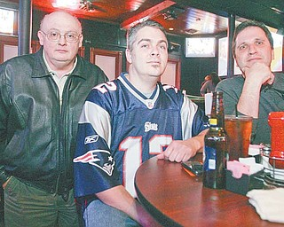 Lou DiNardo, left, Frank Tondo, wearing a Patriots jersey, and John Wojtkowiak, all of Boardman, watch the Super Bowl on Sunday at the Youngstown Sports Grille, a Boardman bar and restaurant.