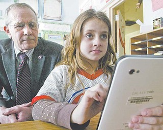 Third-grade teacher Ashley Wallace's students at Lynn Kirk Elementary School in Austintown are using Samsung Galaxy tablets in class as part of a pilot program to test the device's uses in the classroom. Angelina Diana, above, works on the Galaxy while school-board member Dave Schnurrenberger looks on. Two other district teachers — one at Austintown Middle School and one at Fitch High School — also are testing the tablets, Superintendent Vince Colaluca said.