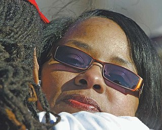 Shirlene Hill, mother of Jamail Johnson, a Youngstown State University senior who was murdered a year ago Monday, is embraced during a march in her son's memory and a plea to stop area violence.