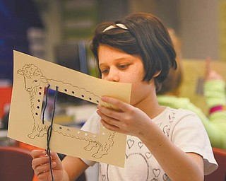 Delilah Lopez, a third-grader at Struthers Elementary School, shows how to make a loom.