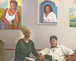 Joseph L. Thomas, 91, of Youngstown, and his wife, Gwendolyn, pose below two of his art pieces — singer Stephanie Mills and Oprah Winfrey — on display for Black History Month at the Dandridge Burgundi Manor care center on Maranatha Court on the city's East