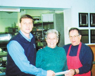 "Slovak Ladies benefit: Bernie Demechko, center, presents a $5,000 check to Brian Antal, left, president of the Mahoning County Saint Vincent de Paul Society, and Ralph Barone, St. Vincent de Paul dining hall manager. Demechko is the district president of the First Catholic Slovak Ladies Association of Beachwood, Ohio, a nonprofit financial benefit society. The dining hall serves more than 90,000 meals annually and its food pantry distributes food to 8,500 people. It also distributes 100 sack lunches daily to after-school ""latchkey"" students from area schools. The FCSLA distributed $1,000,000 in donations at its October convention in Baltimore."