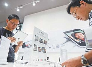 Customers try out iPads at an authorized Apple dealer outlet in Changsha in south China's Hunan province. Authorities have seized iPads from more Chinese retailers in February in an escalating trademark dispute between Apple Inc. and a struggling local company that could disrupt global sales of the popular tablet computer.