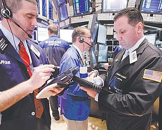 Traders work on the floor of the New York Stock Exchange. The Dow Jones industrial average has soared