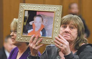 Family member Trish Boone holds a photo of Willie Robinson duringsentencing Feb. 16 in Cleveland for his parents, William Robinson Sr. and Monica Hussing, formerly of Warren. The parents of the 8-year-old