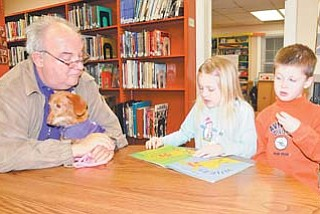 Bill Leskanic, left, of Boardman and his dog, Periwinkle, listen as Carli Hamilton, 7, and Cole Hamilton, 5, both of Boardman read to Periwinkle. They were taking part in Monday's Tales for Tails gathering at the Canfi eld branch of the Public Library of Youngstown and Mahoning County.