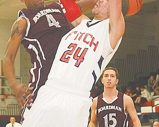 Boardman defender T.J. Irving (4) blocks a shot by Austintown Fitch's Nate Blair during Tuesday's game in Austintown. The Falcons won the rivalry game, 67-37.