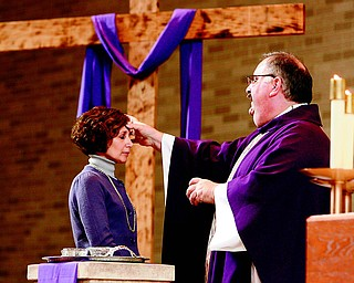 "With the words, ""Repent, and believe the Gospel,"" the Rev. Philip Rogers, of St. Charles Borromeo Church in Boardman, makes the sign of the cross in ashes on the forehead of Ann Moran of Boardman during a noon Ash Wednesday Mass. Ash Wednesday is the start of Lent."
