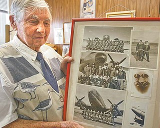 David Hall, Girard city engineer, holds a frame depicting three of the nine planes he flew during and just after World War II when he was in the U.S. Army Air Corps. Hall has been with the city for 12 years.