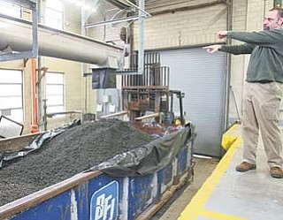 Howard Zickefoose, acting superintendent of the Girard waste-water treatment plant, shows the final processed waste product to be sent to a landfill. The new equipment is expected to generate about $180,000 in additional revenue for Girard annually.