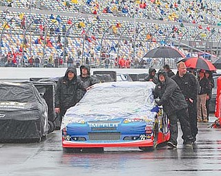 Crew members push driver Elliott Sadler's car down the starting grid in the rain in preparation for Sunday's NASCAR Daytona 500 Sprint Cup series auto race at Daytona International Speedway in Daytona Beach, Fla. The race was postponed to today.