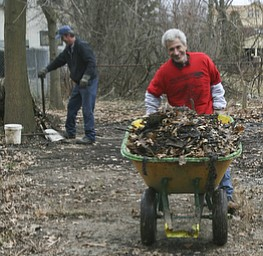 JESSICA M. KANALAS  | THE VINDICATOR..Blake, new to the North side, wheels a load of garbage and debris to a dumpster during a clean-up day held at his home on Lora Ave.
