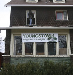 JESSICA M. KANALAS  | THE VINDICATOR..Ron Major of the North side replaces windows on the second floor of Blake's new home. Major works for Youngstown Contracting which donated their workers time to come out and help the crew fix up the new house on Saturday.