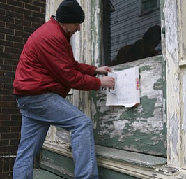 JESSICA M. KANALAS  | THE VINDICATOR..Volunteer Bob Harrell of Youngstown puts a sign on a side door after replacing the glass window.