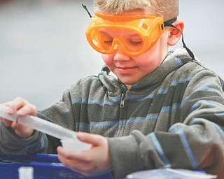 "Jacob Scolville, a fourth-grader at E.J. Blott Elementary in Liberty, mixes his own batch of slime in the gymnasium. On Wednesday, the Center on Science Industry's traveling exhibit called ""It's Simple Chemistry"" brought hands-on science activities to the students."