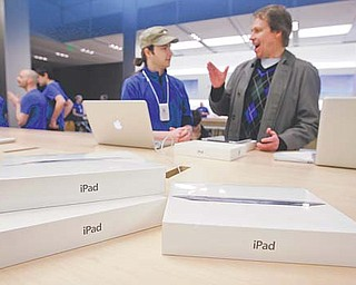 A customer talks with an Apple worker, in blue, at an Apple store on the first day of the launch of the new iPad, in San Francisco. A research firm that has taken apart a new iPad says it's more expensive to make than the previous version was when it launched a year ago. The tablet's retail price is the same, so that means Apple is making less from each sale. Since the first iPad, Apple has been pricing the tablet aggressively, making it hard for competitors to match its features for the same price.