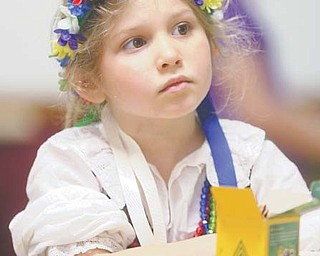 Kataryna Flasher, 6, of Youngstown, above, watches the palm-weaver demonstration during the Polish Easter Traditions Workshop and Celebration on Sunday.