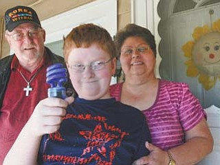 """Edwin """"J.J."""" Gurney Jr., 12, shows off the blue light he and his parents want people to purchase and shine on outdoor porch lights and lampposts Monday, which is World Autism Awareness Day. J.J., who has Asperger's syndrome, a form of autism, is flanked by his father, Edwin Sr., and his mother, Peggy Gurney."""