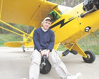 Gordon Murray, a Girard native, is shown with his vintage Piper Cub plane he will fly to each of Ohio's 88 counties beginning May 13. Murray and Ron Siwik of Chagrin Falls, who will fly another vintage plane, are making the trip to raise funds to establish a scholarship for a needy Ohio family to send a child to college. The team expects to land at Youngstown Elser Metro Airport in North Lima on May 15.