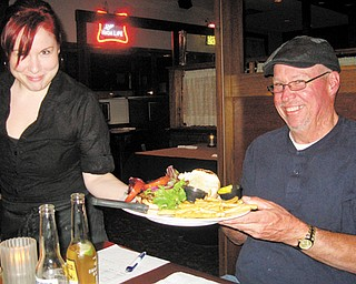 Heather Bornes hands Scott Long his burger for review.
