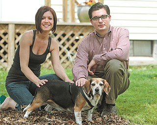 Alison Morris and her friend Nathaniel Riggle pose with Toby, one of two beagles attacked by a pit bull in Morris' yard. The attack left both with a decreased sense of security.