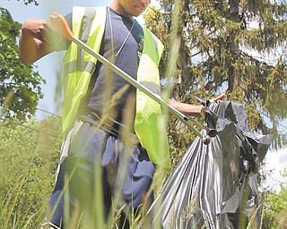 Emmett Conner, a senior at the Choffin Career and Technical Center, helps remove garbage from a vacant lot on Youngstown's South Side. About 20 Choffin seniors participated in the cleanup Thursday.