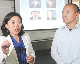 Youngstown State University professors Helen Han and Peter Chen have completed a paper on how chief executive officers' portraits form individual views on a company's success. They addressed a class at YSU recently. Portraits of CEOs are projected behind them.