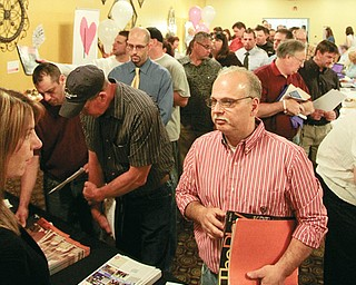 The line to speak to officials from Chesapeake Energy stretches out the door at the job fair that was part of the Columbiana County Economic Development Summit. The event had filled the parking lot at the East Liverpool Motor Lodge well before the fair's 10 a.m. Monday start.