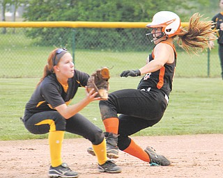 Howland's Emily Price (9) slides into second base past Cuyahoga Falls' Hannah Shane (1) during a Division I tournament softball game Monday at Howland Township Park. Freshman Hannah Burke tossed a no-hitter to lead Howland to the 10-0 victory.