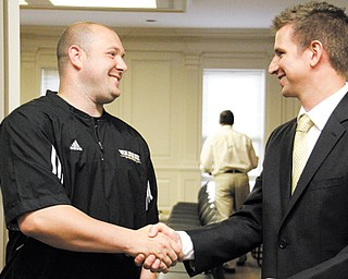 Frank Caputo, left, and Andy Vlajkovich shake hands after being named the new girls and boys basketball coaches, respectively, at Warren Harding High School during a board of education meeting at the Warren administration building Tuesday.