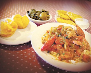 Monteen's Southern Cuisine's signature Jambalaya dish served on a bed of rice topped with andouille sausage, fresh tomatoes, okra, celery, peppers and crawfish. Served with a side of breaded fried green tomatoes and collard greens.
