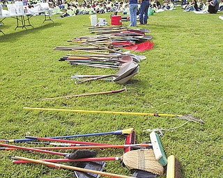 Brooms, rakes and shovels lie waiting for more than 300 students from Heartland Christian School at Firestone Park in Columbiana. Students, listening to director of school and community relations Linda Brandenstein, gathered at the park Wednesday to weed, paint and clean for School Service Day.