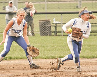 Hubbard's Samantha Dudley, left, watches as teammate Taylor Barton scoops up a ground ball near a muddy second base during the top of the seventh inning in their Division II tournament softball game Wednesday against Niles at Harding Park in Hubbard. The Eagles downed the Red Dragons, 5-2.