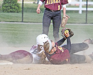 Stevie Taylor of South Range shows the ball to the umpire after she tagged out Liberty baserunner Allyson Solarz during a Division III sectional softball game Thursday in Beaver Township. The Raiders blanked the Leopards, 10-0.