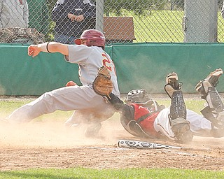 Drew DelSignore (22) of Mooney is tagged out at home by Struthers catcher Cody Bova during their Division II sectional semifinal baseball game Thursday at Cene Park in Struthers. The Cardinals defeated the Wildcats, 15-2, to advance to the final today against Niles at Waddell Park.