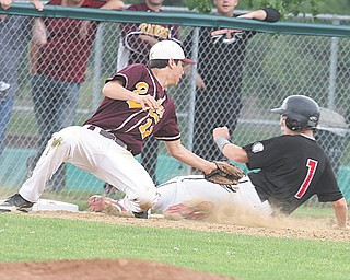 Jim Standohar (1) of Girard slides in behind the tag of South Range's Mason Miller (12) during their Division III district semifinal baseball game Monday at Cene Park in Struthers. The Indians blanked the Raiders, 10-0, and advance to play Ursuline in the district championship today.