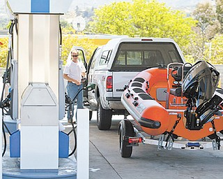 Travelers fill up at a gas station for an early start on the Memorial Day weekend traffic in Valencia, Calif. This year, economists and tourism experts are expecting only a small uptick in summer travelers. Gas prices are lower but still high enough to keep some Americans off the road.