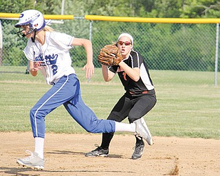 Poland's Meredith Tesone (2) narrowly avoids being tagged out as Canfield shortstop Rachel Tinkey fields a line drive during the Division II district final softball game Wednesday at Alliance High School. Tinkey had two hits for the Cardinals, who lost to the Bulldogs, 8-1. Poland starting pitcher Erin Gabriel, the reigning Ohio Player of the Year, dominated the Cardinals with a complete game that included 15 strikeouts.