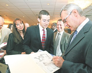 Jim Tressel, former Youngstown State and Ohio State football coach, autographs a drawing for Anthony Lattanzio, 15, of Poland at the United Way's Champions Among Us dinner Thursday at Mr. Anthony's in Boardman. Also speaking at the fundraiser was Penn State senior running back Michael Zordich, a graduate of