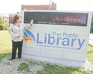 Janet Loew, communications and public-relations director, shows off the new electronic event sign in front of the main library on Wick Ave.