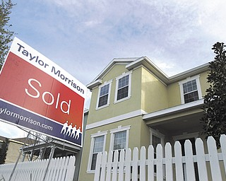 "A ""sold"" sign stands outside a home in Riverview, Fla. Americans bought more previously owned homes in