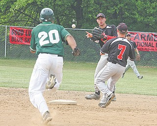 Canfield's Joe Tuchek flips the ball to teammate Mike Ross (7) as Ursuline's Paul Pegues (20) heads toward second base during Tuesday's game in Canfield.